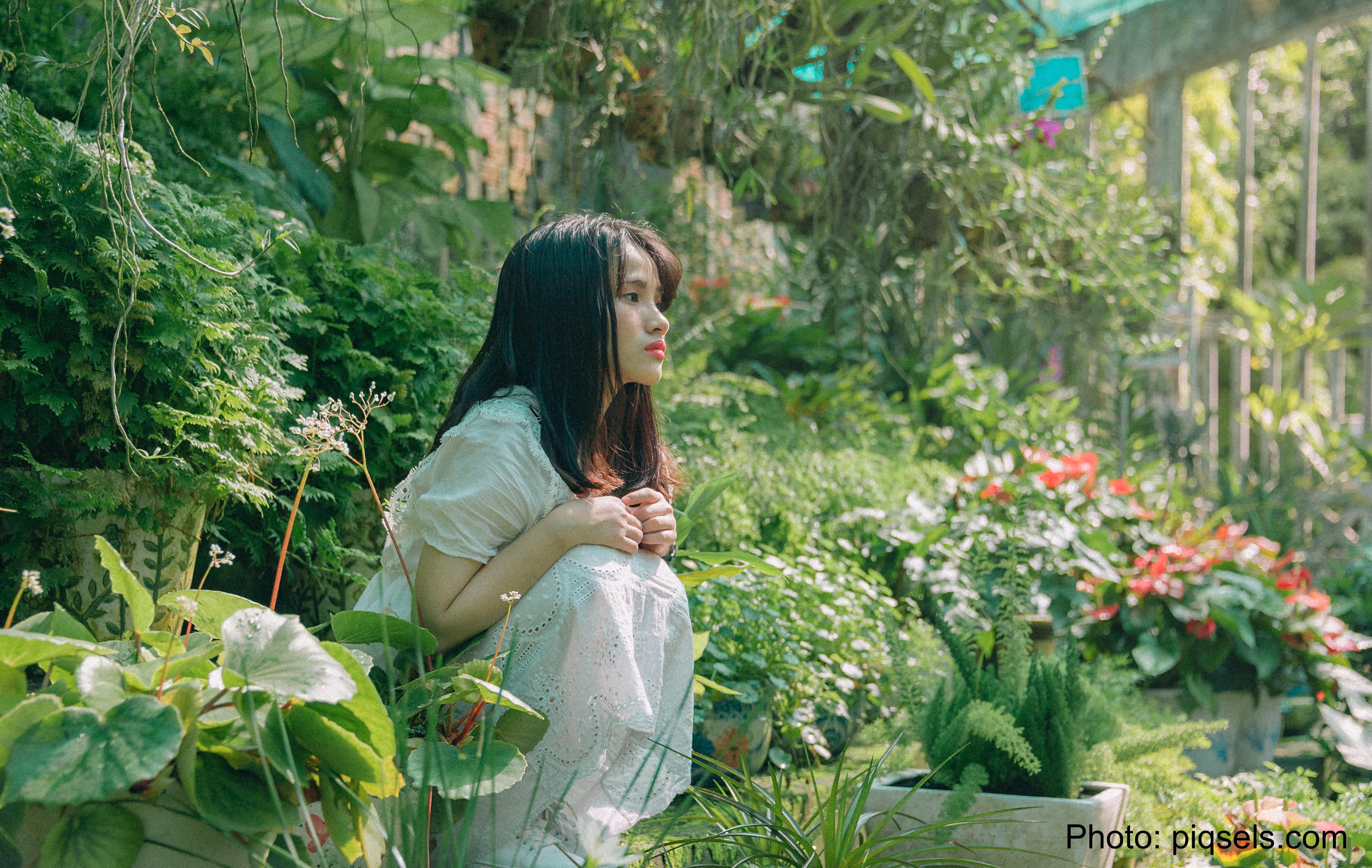 Pensive woman in flower garden.